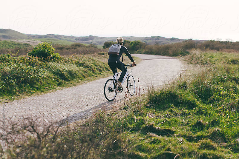 Man riding his bicycle on a path through the dunes by Denni Van Huis for Stocksy United