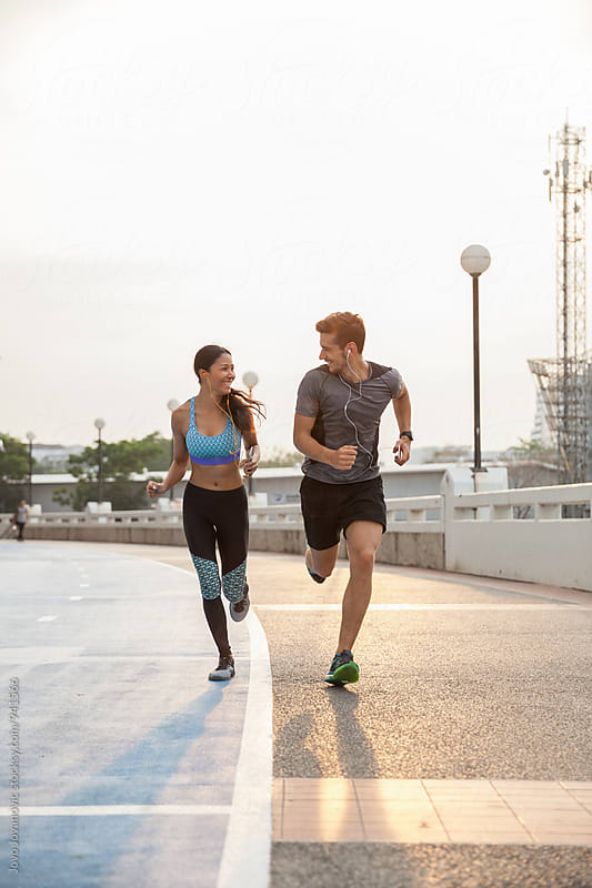 Couple running together outdoors by Jovo Jovanovic for Stocksy United