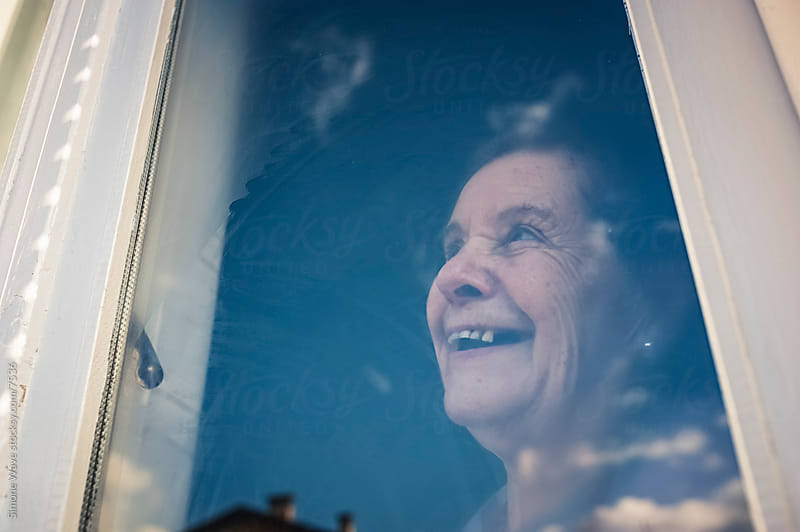 Happy Senior Woman Portrait at window by Simone Becchetti for Stocksy United