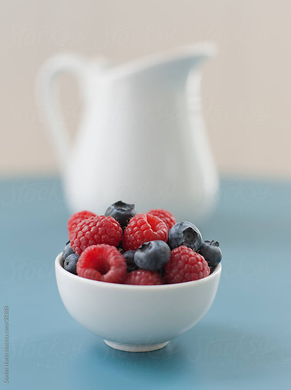 Bowl of berries and porcelain pitcher by Daniel Hurst for Stocksy United