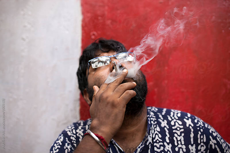 A man smoking cigerrate by PARTHA PAL for Stocksy United