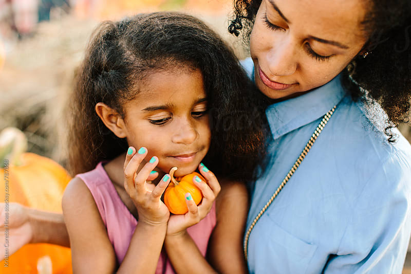 A mother holding her young daughter at a pumpkin patch by Kristen Curette Hines for Stocksy United