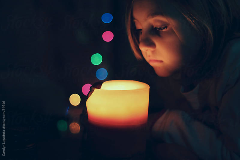 Young girl looking into a candle with lights behind her by Carolyn Lagattuta for Stocksy United