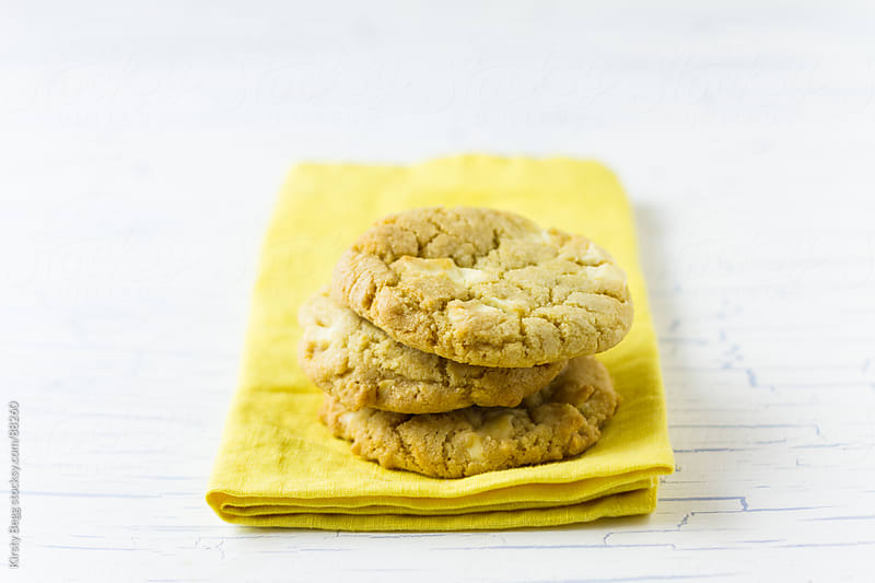 Trio of White Chocolate cookies on yellow napkin by Kirsty Begg for Stocksy United