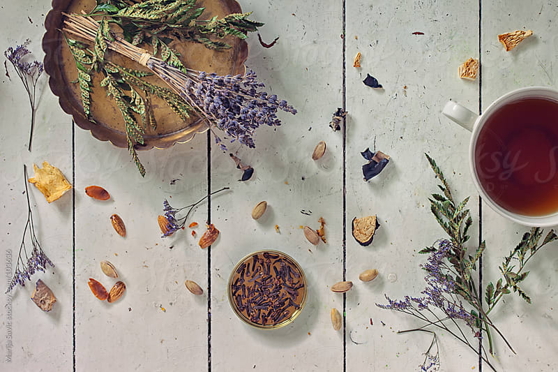 Nuts, tea and flowers on a wooden table. by Marija Savic for Stocksy United