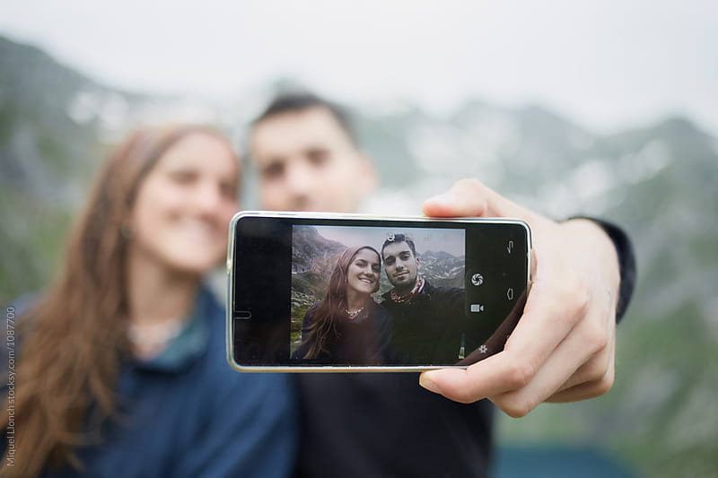 Young couple taking a selfie outdoors in the mountains by Miquel Llonch for Stocksy United