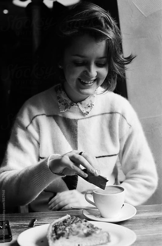 A black and white film photo of young smiling woman putting sugar in coffee in the coffeehouse by Anna Malgina for Stocksy United