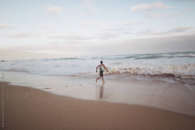 Man with surfboard running into ocean to surf by Rob and Julia Campbell for Stocksy United