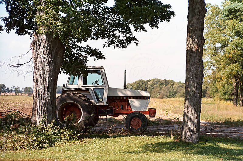 An old tractor parked under a tree by Riley J.B. for Stocksy United