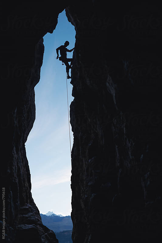 Alpinist silhouette climbing a rock cave entrance outdoor by RG&B Images for Stocksy United