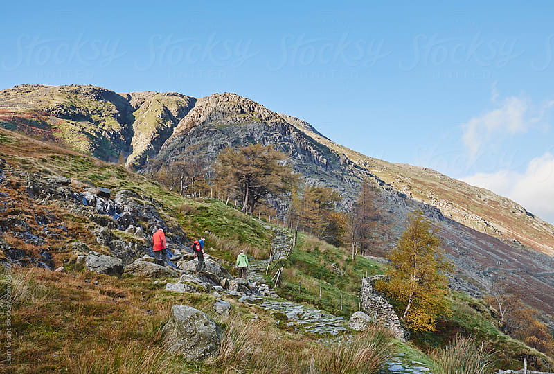 Three people on a footpath in the mountains. Cumbria, UK. by Liam Grant for Stocksy United
