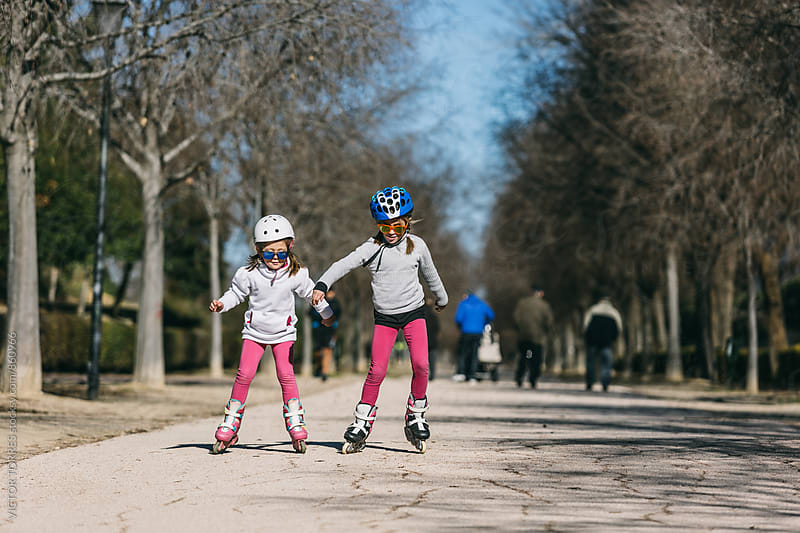 Two Sisters Roller Skating in the Park by Victor Torres for Stocksy United