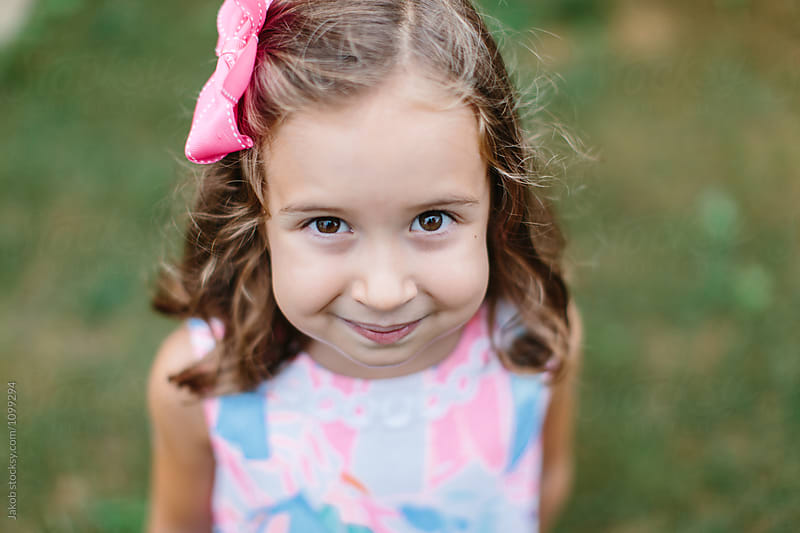 Beautiful young girl with a bow in her hair looking up at the camera by Jakob for Stocksy United