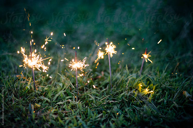 Sparklers in the grass by Cara Dolan for Stocksy United