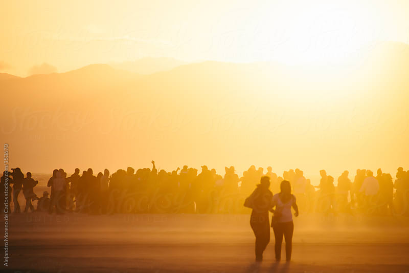 Group of people having fun at the beach on a music concert at sunset. Silhouette people by Alejandro Moreno de Carlos for Stocksy United