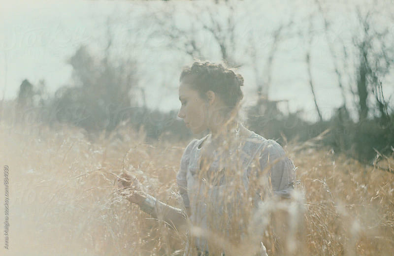 A film portrait of a young beautiful woman in the grass by Anna Malgina for Stocksy United