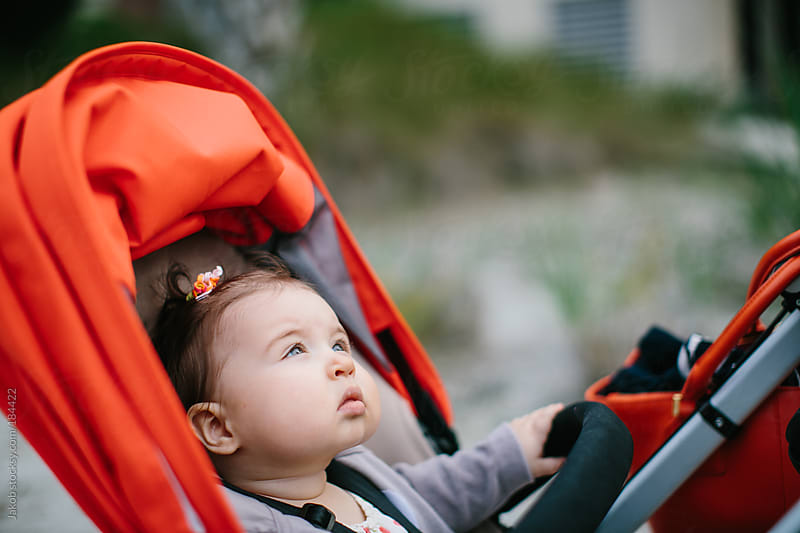 Baby looking up from her stroller by Jakob for Stocksy United