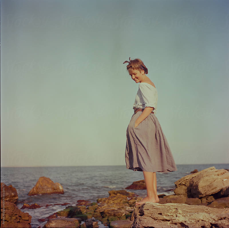 A film portrait of a young beautiful woman standing in front of the sea by Anna Malgina for Stocksy United