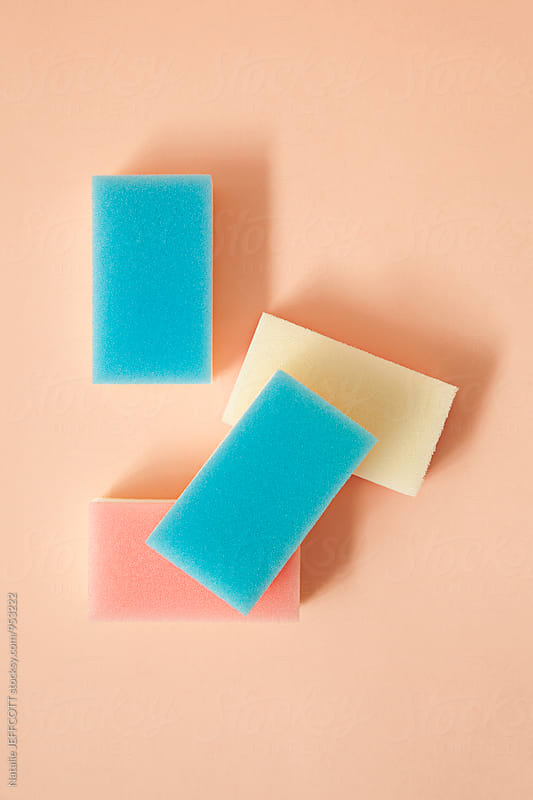 Household cleaning sponges arranged on a pink background by Natalie JEFFCOTT for Stocksy United