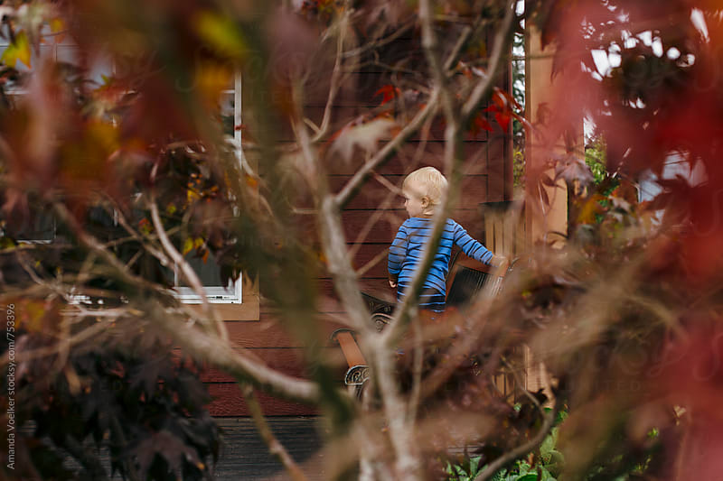 Toddler Sits on Front Porch, Hidden By Trees by Amanda Voelker for Stocksy United