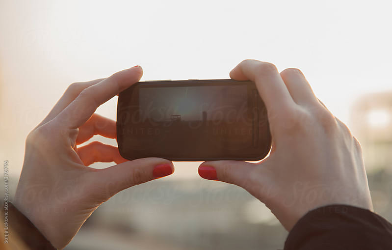 taking a cell phone photo of a sunset closeup by Sonja Lekovic for Stocksy United