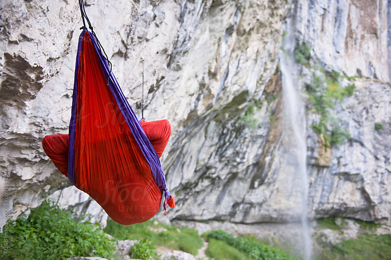 Person relaxing in a hammock outdoor near a waterfall by RG&B Images for Stocksy United