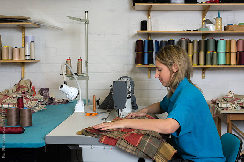 Machine sewing fabric in a furnishings company. by Paul Phillips for Stocksy United