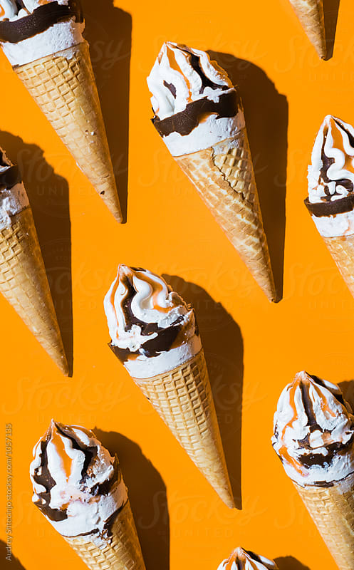 Caramel vanilla and chocolate ice creams on orange background. by Audrey Shtecinjo for Stocksy United