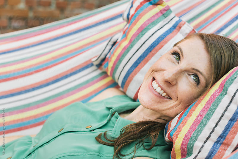 Young woman lying in a hammock, smiling by Lilly Bloom for Stocksy United
