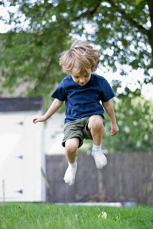 Child wearing socks and no shoes jumps around in his backyard by Cara Dolan for Stocksy United