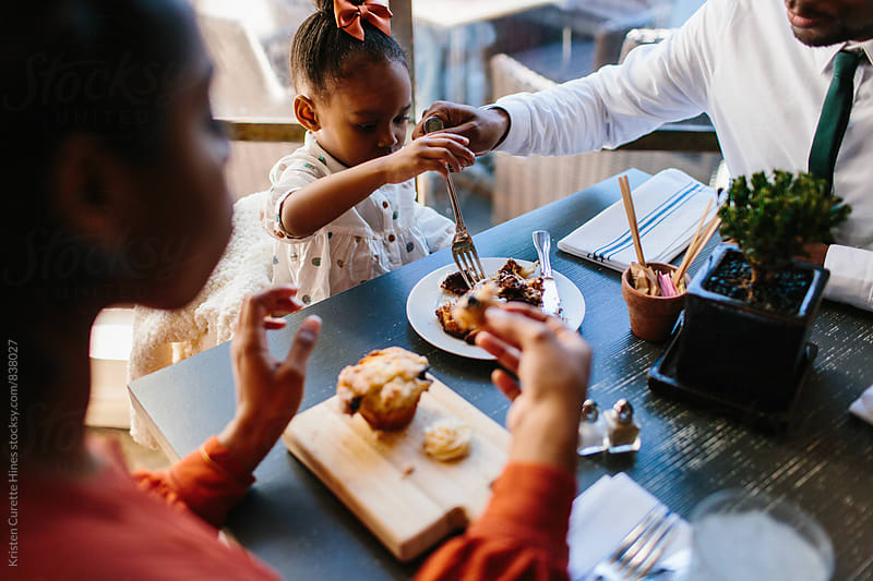 A family of three eating breakfast at a cafe by Kristen Curette Hines for Stocksy United