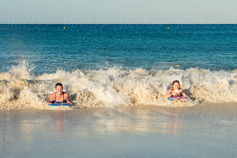 girls bodysurfing at the beach, one of them is making a video on her mobile phone as she surfs by Gillian Vann for Stocksy United