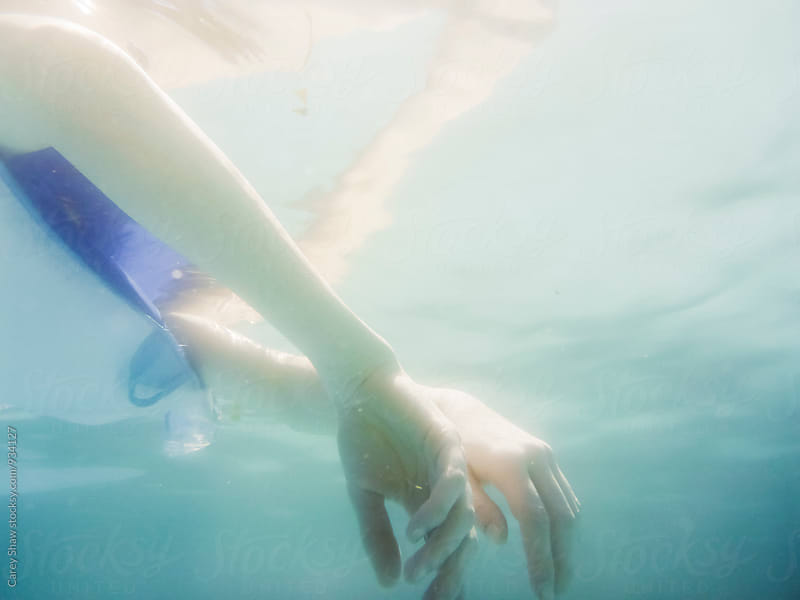 Underwater view of woman floating in pool by Carey Shaw for Stocksy United
