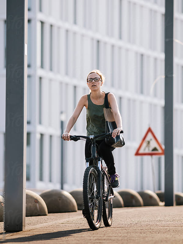 Woman commuting to work by Bicycle by VegterFoto for Stocksy United