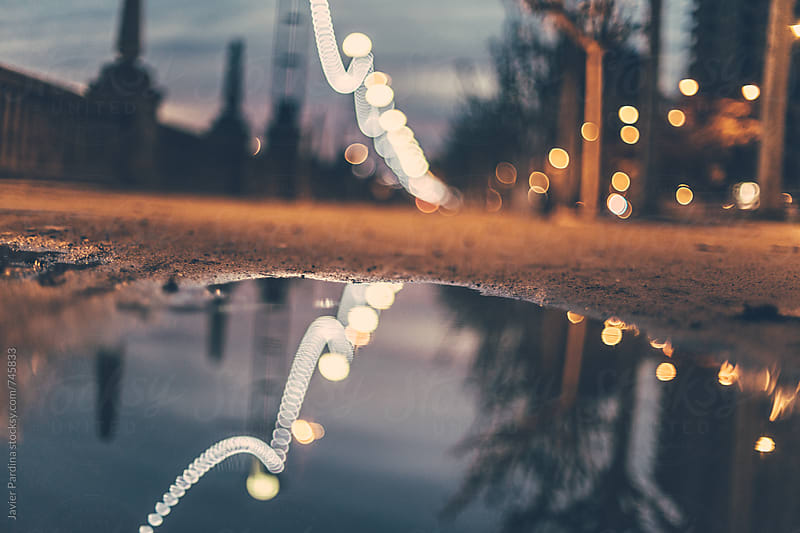 Reflected street lights on the little puddle by Javier Pardina for Stocksy United