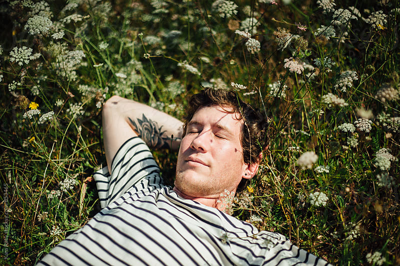 Man lying in a meadow by Kara Riley for Stocksy United