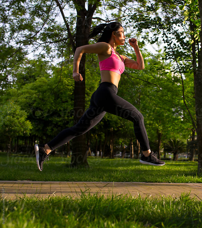 young asian woman running in the park by cuiyan Liu for Stocksy United