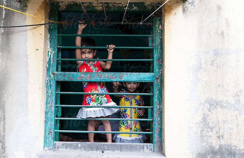 Twin girls holding windows and making fun by PARTHA PAL for Stocksy United