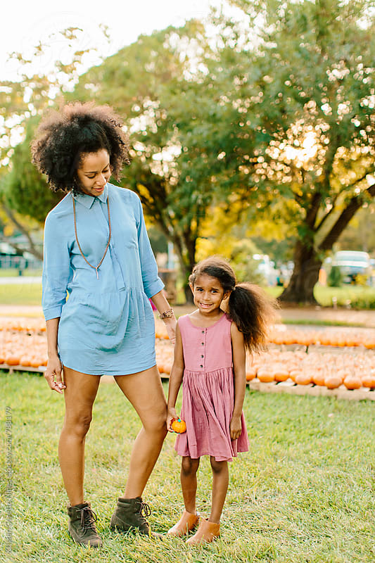 Portrait of a mother and daughter at a pumpkin patch by Kristen Curette Hines for Stocksy United