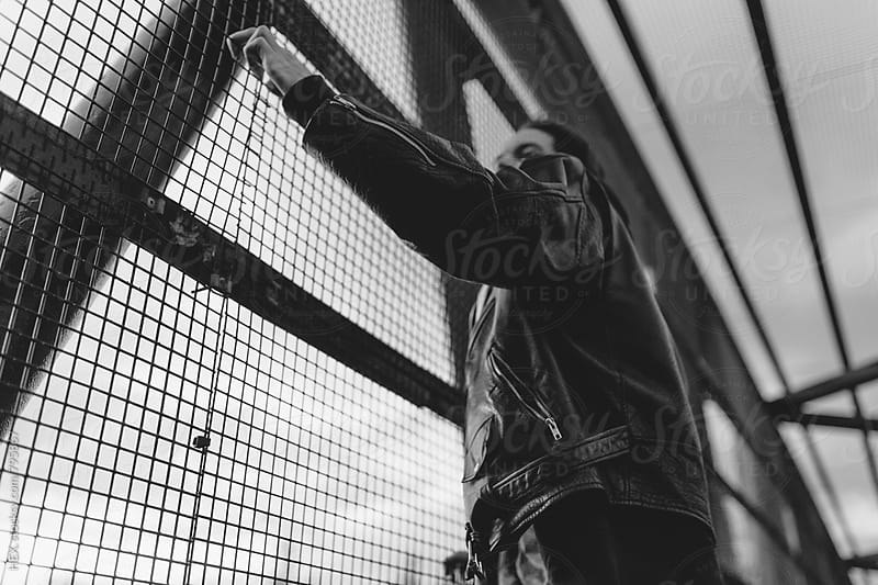Young Man Climbing a Bridge Cage over an Highway by HEX. for Stocksy United