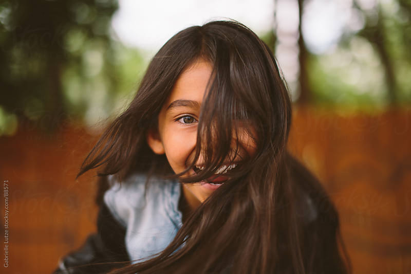 Young Girl Smiling with Hair in Face by Gabrielle Lutze for Stocksy United