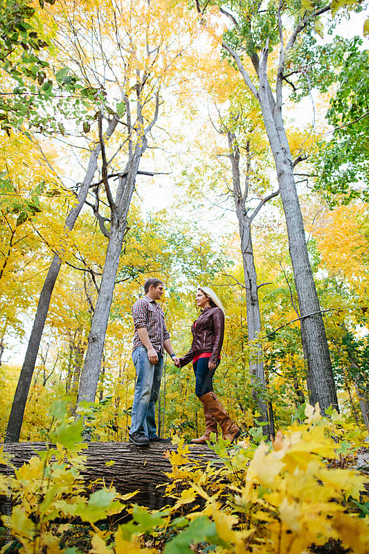 couple holding hands among the trees by Brian Powell for Stocksy United