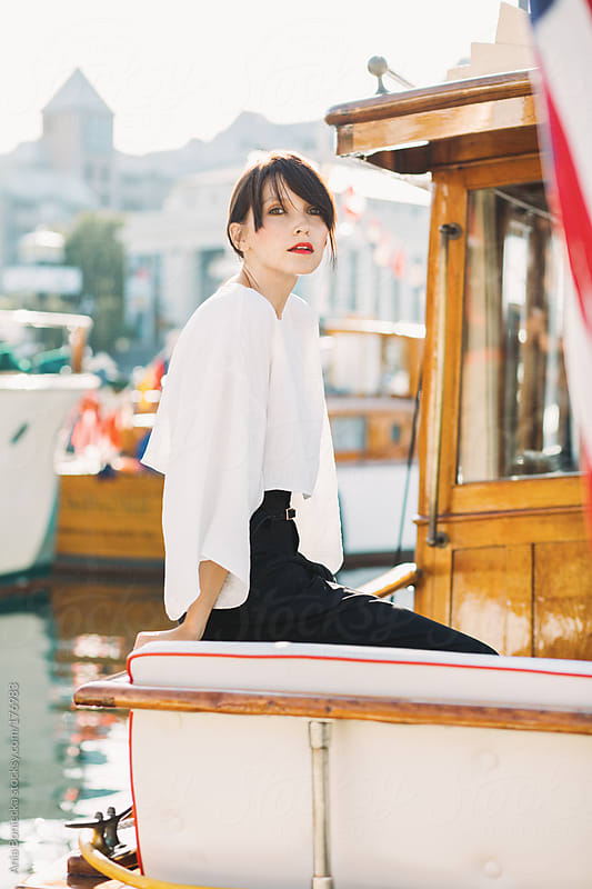 Beautiful woman on an old wooden boat with a city in the background by Ania Boniecka for Stocksy United