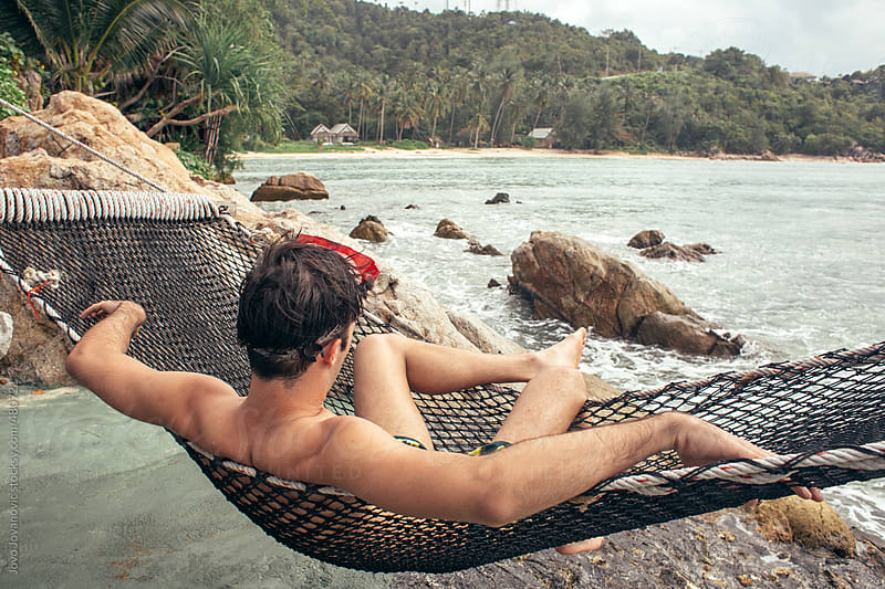 Young man chilling on a hammock on a rocky cliff overlooking the ocean and an island by Jovo Jovanovic for Stocksy United