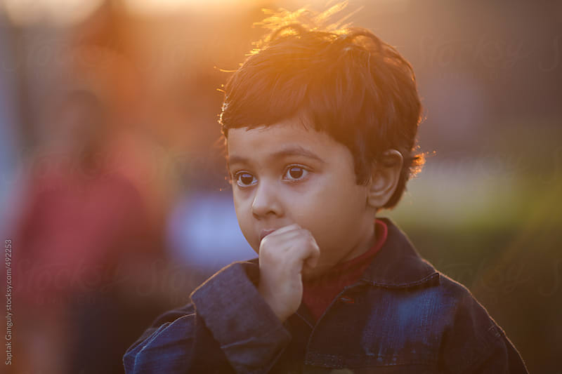 Close up portrait of cute toddler in a sad mood by Saptak Ganguly for Stocksy United