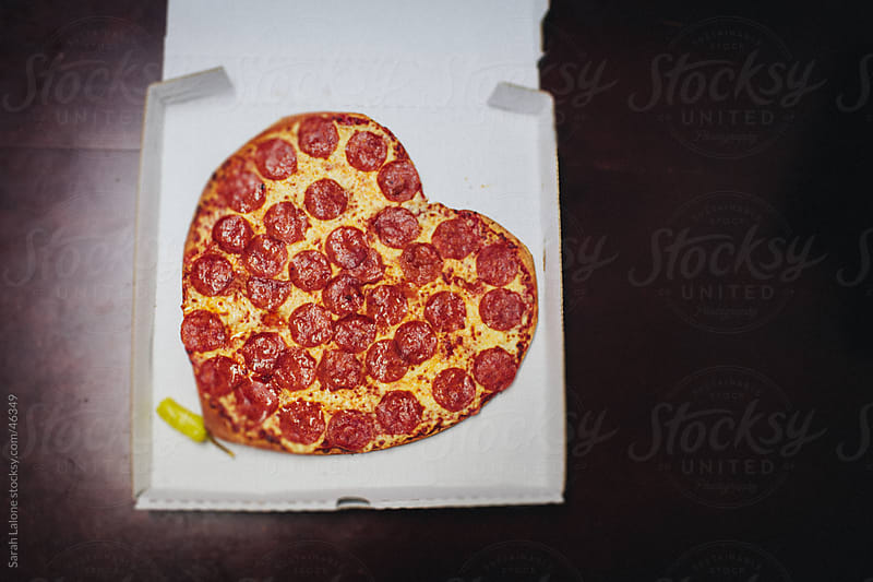 A heart shaped pizza in the box on a table. by Sarah Lalone for Stocksy United