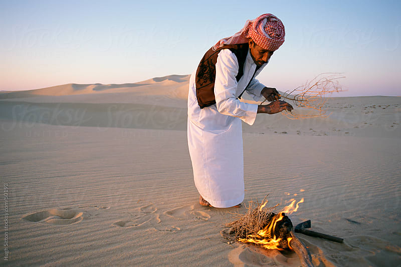Arab making fire in desert. by Hugh Sitton for Stocksy United