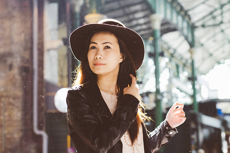 Asian lady in the rain wearing a floppy hat adjusting her hair at Borough Market, London by Maresa Smith for Stocksy United