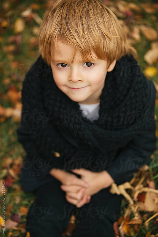 A portrait of a young boy sitting on leaf covered grass looking up by Ania Boniecka for Stocksy United