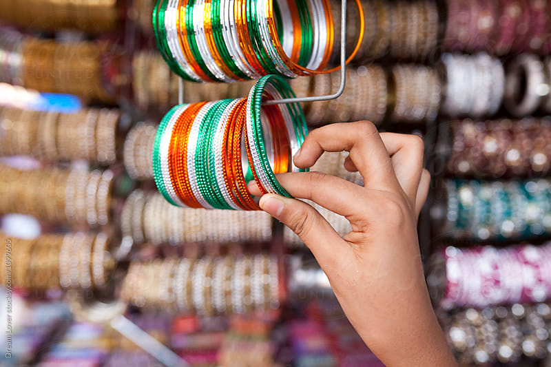 Teenage girl holding colorful bangles by PARTHA PAL for Stocksy United